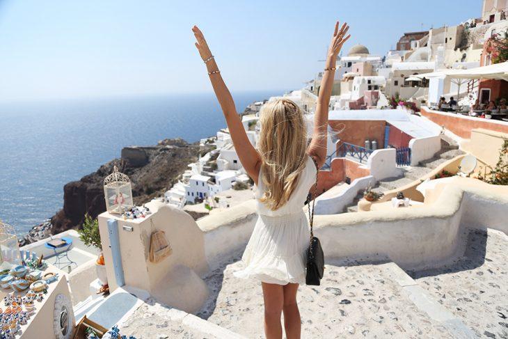 Chica viendo el mar con las manos levantadas