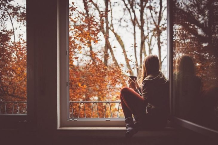 chica pensativa en una ventana