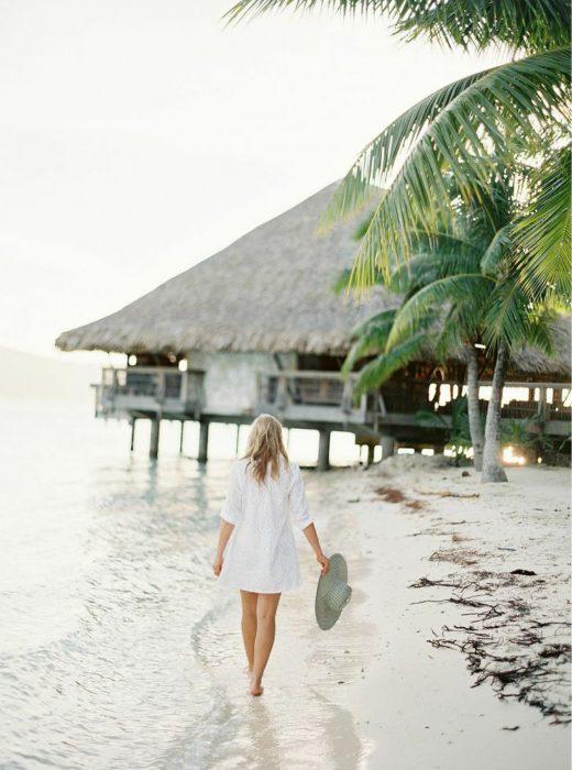 Chica caminando a la orilla de la playa