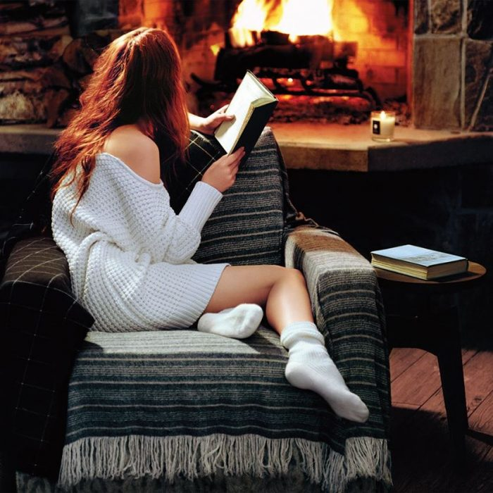chica leyendo un libro frente a una fogata