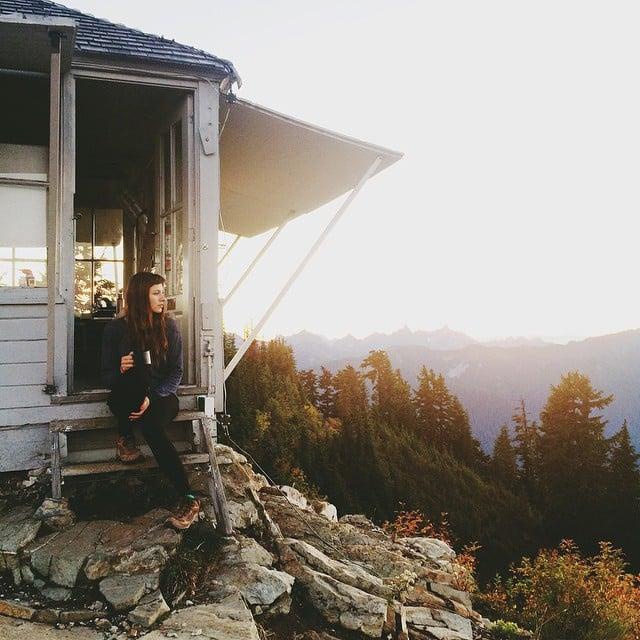 Chica sentada en las escaleras de una cabaña en el bosque