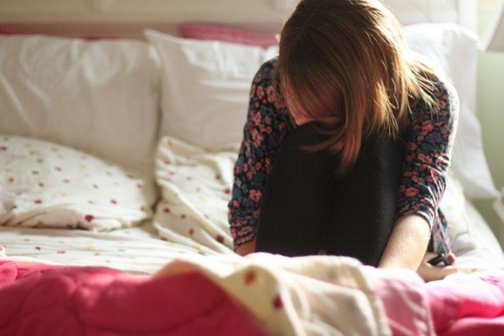 Chica triste sentada en la cama