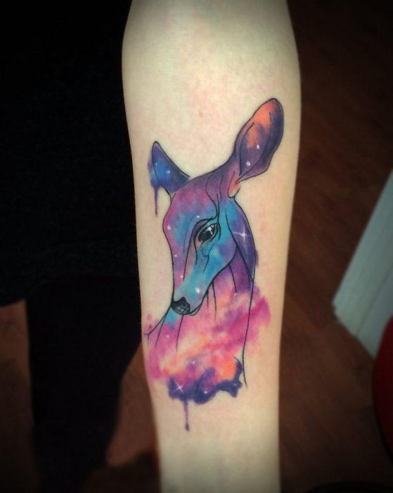 ciervo tatuado al estilo acuarela simulando una galaxia