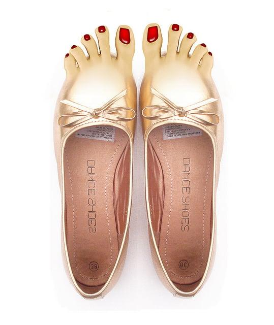 zapatos dorados en la punta tienen unos dedos con uñas de color rojo