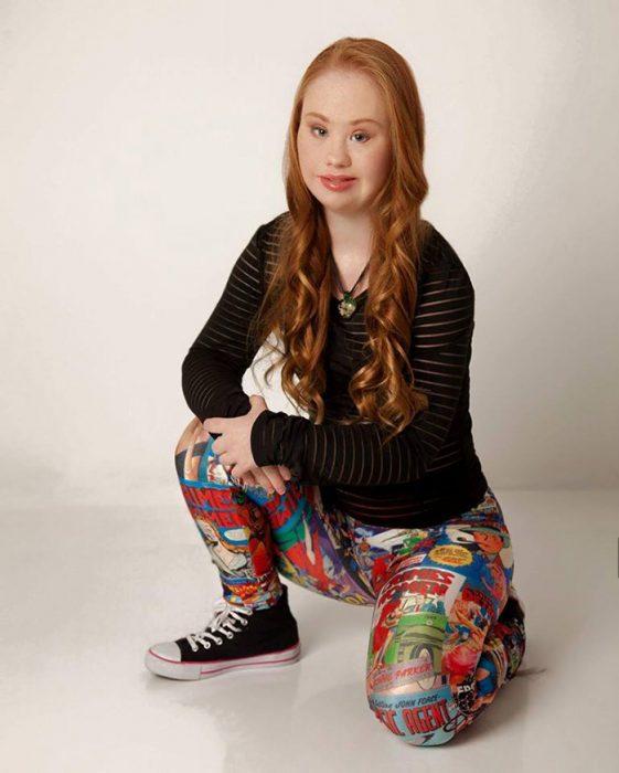 chica con síndrome de Down usando unas mallas de colores y un suéter negro