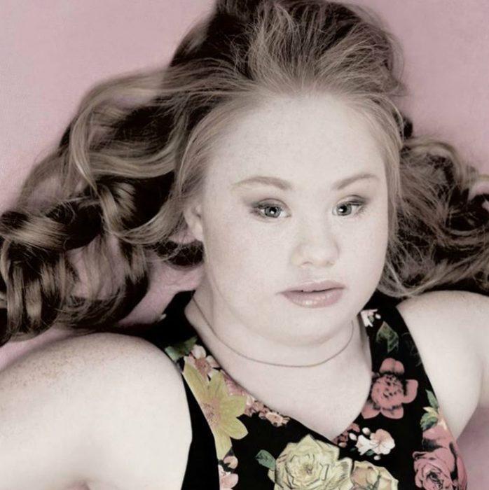 chica con síndrome de down recostada en el suelo