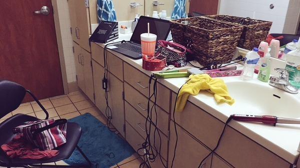 cuarto de baño de una chica con maquillajes y planchas para el cabello tiradas