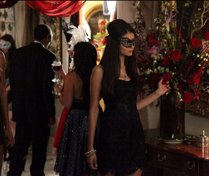 escena de la serie diarios de un vampiro protagonista usando una mascara y tocando unas rosas rojas