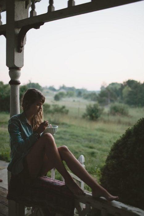 chica sentada en el balcon comiendo un tazón de cereal