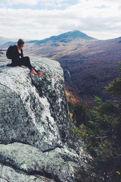 chica sentada en una montaña viendo el bosque