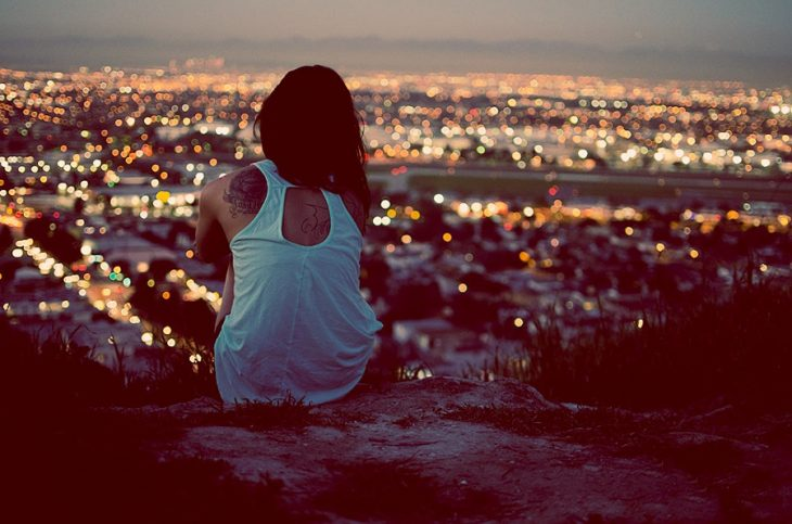 chica sentada en una roca viendo la ciudad