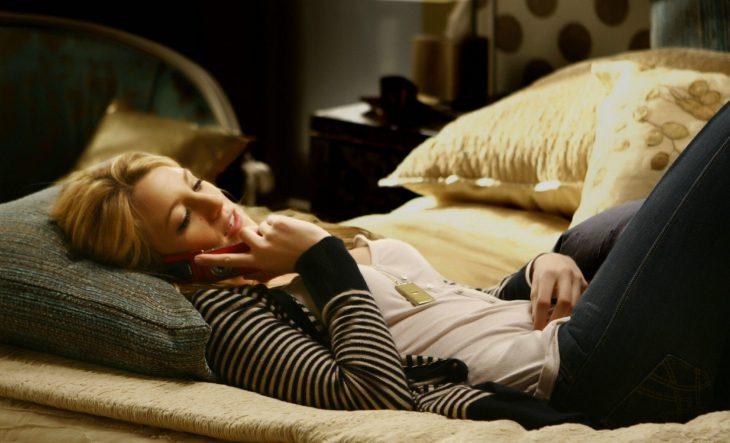 chica recostada en la cama hablando por celular