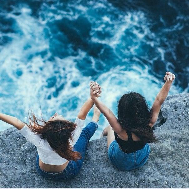 chicas sentadas en una roca viendo el mar y levantado las manos