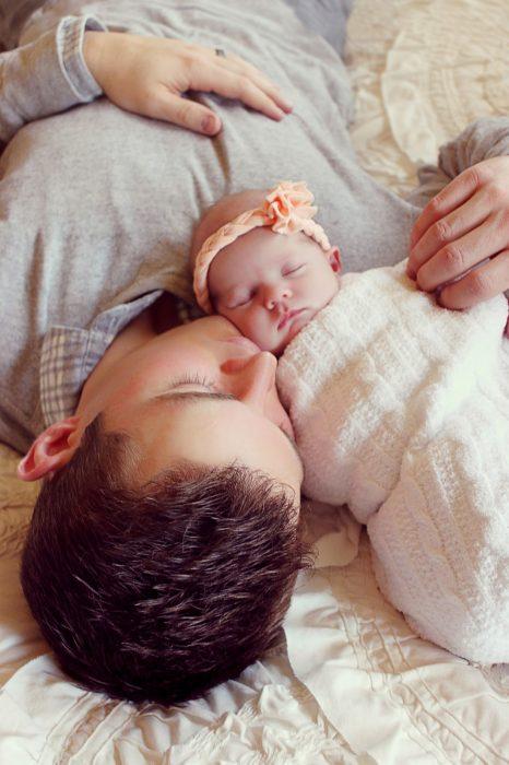 padre e hija bebé acostada en la cama