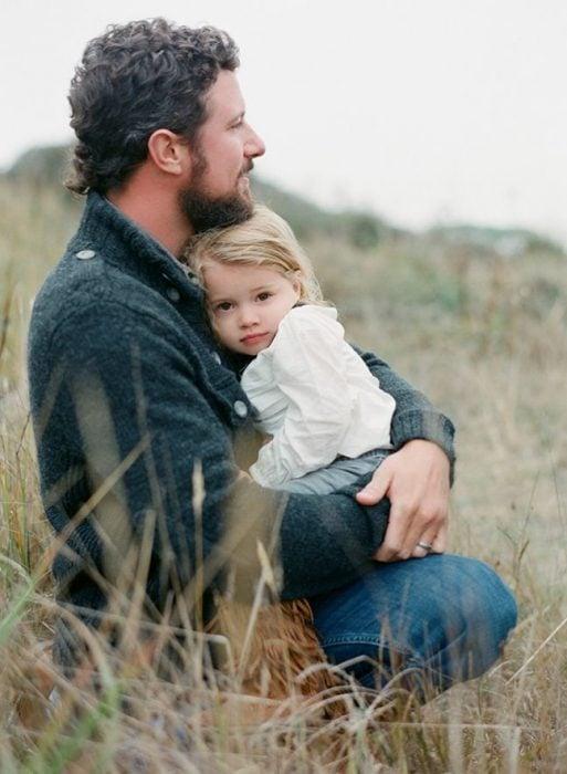 padre e hija abrazados en un campo