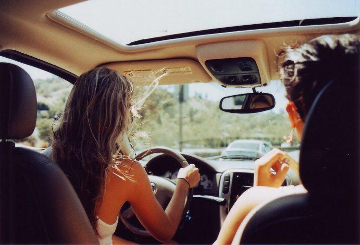 chica conduciendo una camioneta mientras su novio va de copiloto