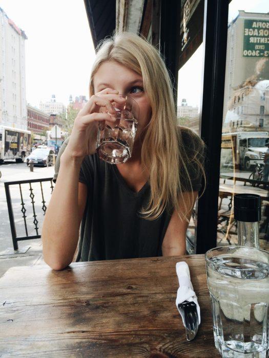 chica bebiendo un vaso de agua en un restaurante