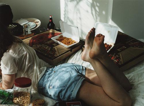 chica recostada en la cama rodeada de cajas de pizza y platos de unicel