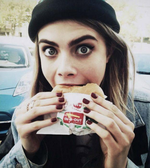 cara delavinge comiendo una hamburguesa