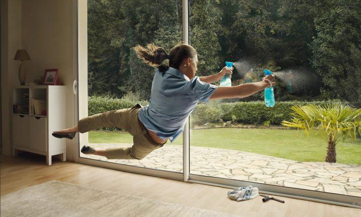 mujer limpiando los vidrios de una casa