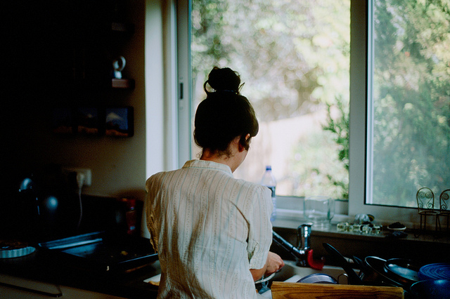 chica lavando los platos frente a una ventana