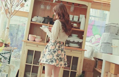chica frente a un estante donde tienen platos