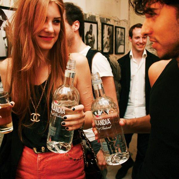 chica sosteniendo una botella de vodka mientras conversa con un chico