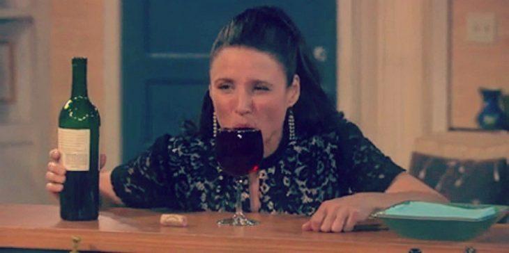 mujer bebiendo una copa de vino sentada en una mesa