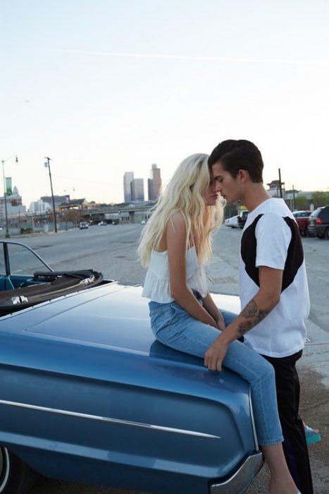 pareja de novios sentadados en un carro besándose