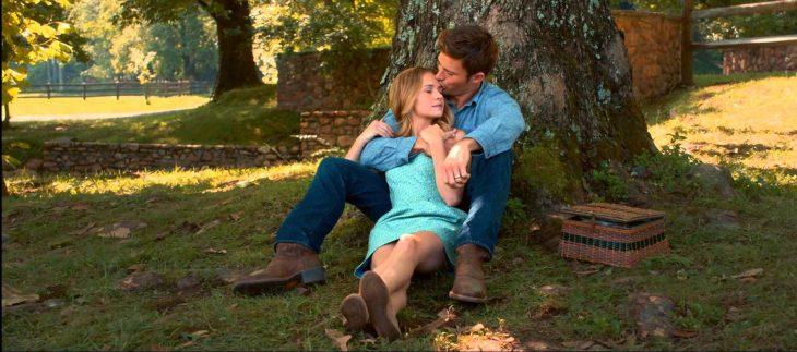 Escena de la película el viaje más largo pareja sentados en el pasto recargados en un árbol