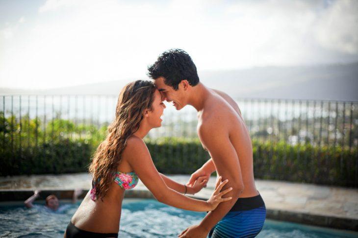 pareja de novios jugando junto a una piscina