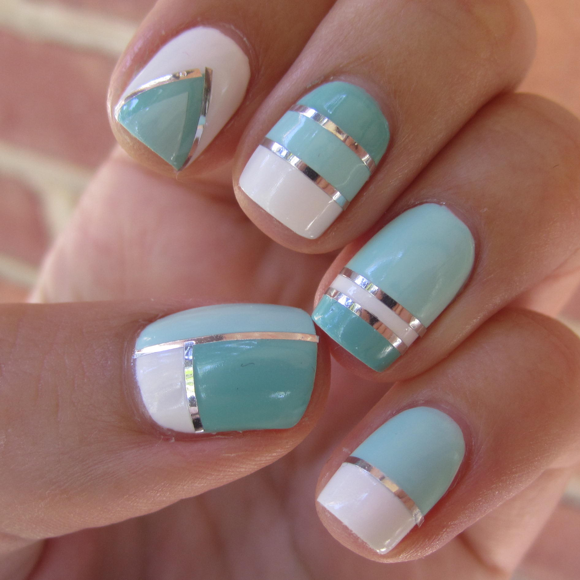 uñas de color blanco con azul y cintas plateadas