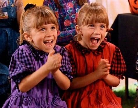 gemelas olsen de niñas usando vestidos rojos y morados