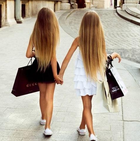 niñas tomadas de las manos con el cabello largo y con bolsas de ropa en las manos