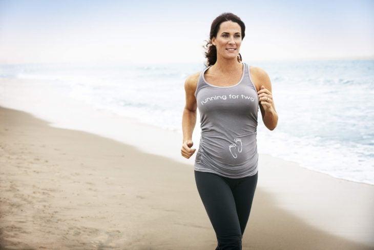 mujer embarazada corriendo por la playa