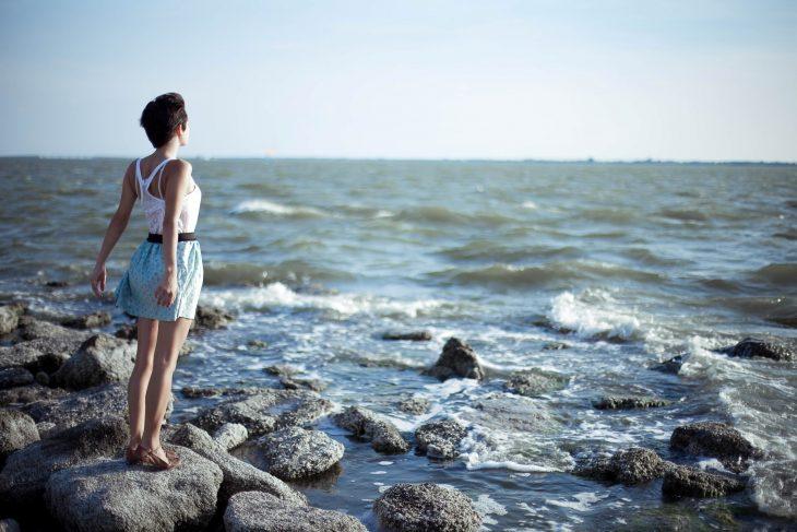 chica parada sobre unas rocas mirando hacia el mar