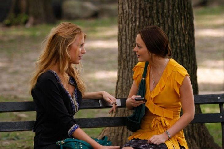 chicas conversando sentadas en la banca de un parque