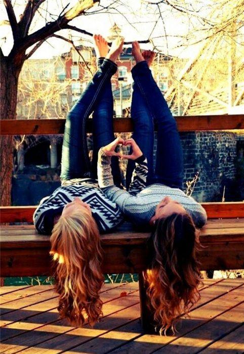 chicas acostadas en una banca con sus cabezas colgando mostrando el cabello