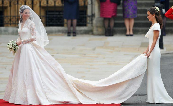 kate midledtonn el día de su boda y su herma sosteniendo la cola del vestido