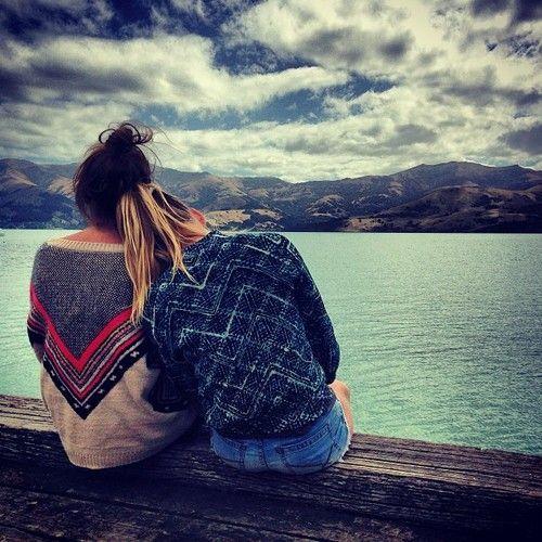chicas sentadas abrazadas viendo el mar