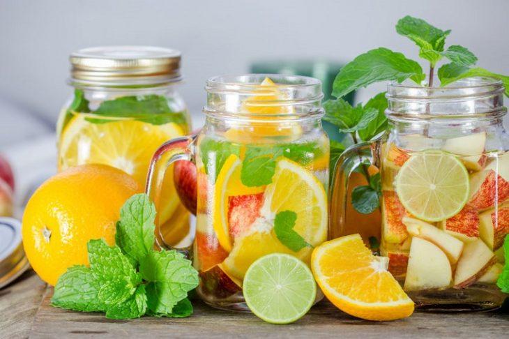 vasos con agua de cítricos como manzana, naranja y limón