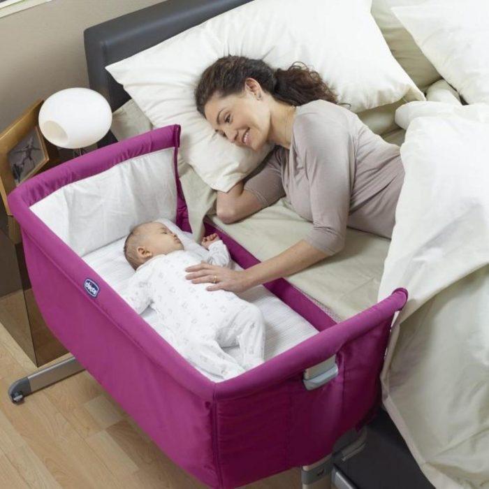 mujer acostada en la cama junto a su bebé