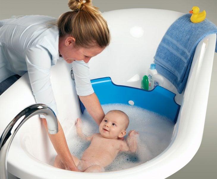 mujer bañando a su bebé en la tina del baño