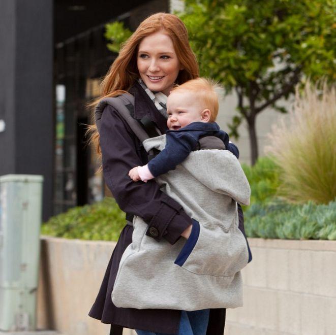 mujer cargando a su bebe en el pecho y cubriéndolo con una sudadera
