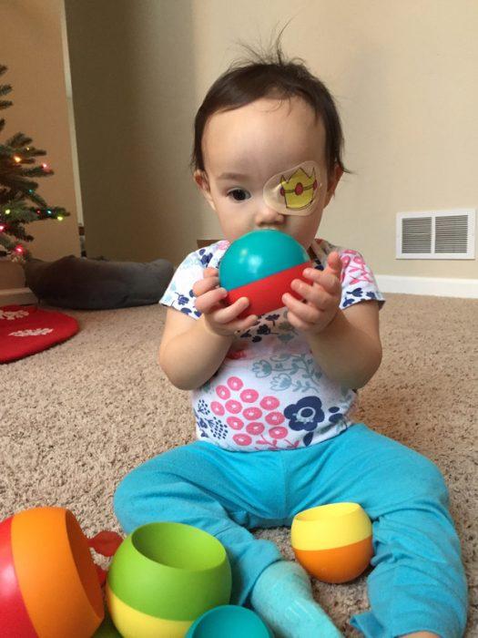 niña usando un parche en el ojo y jugando con una pelota