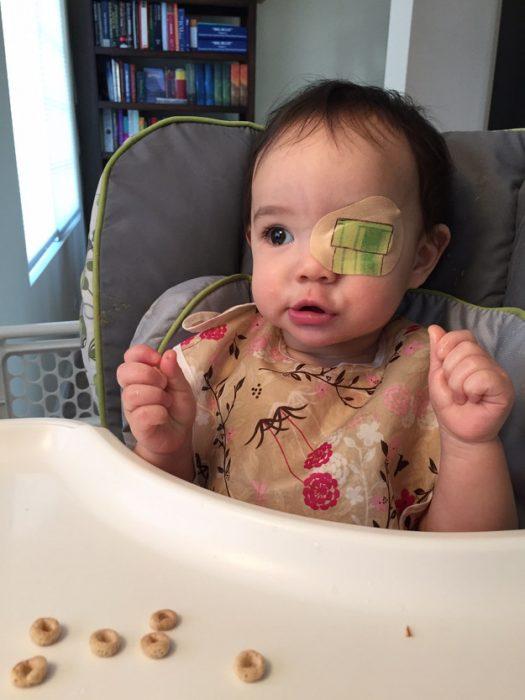 niña usando un parche en el ojo y sentada en una periquera