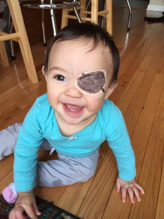 niña senada en el suelo usando un parche en el ojo