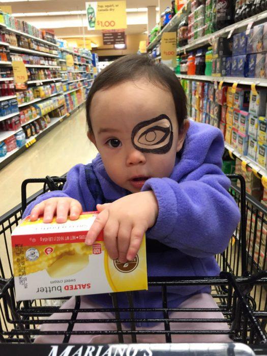 niña sentada en un carrito de super mercado usando un parche en el ojo