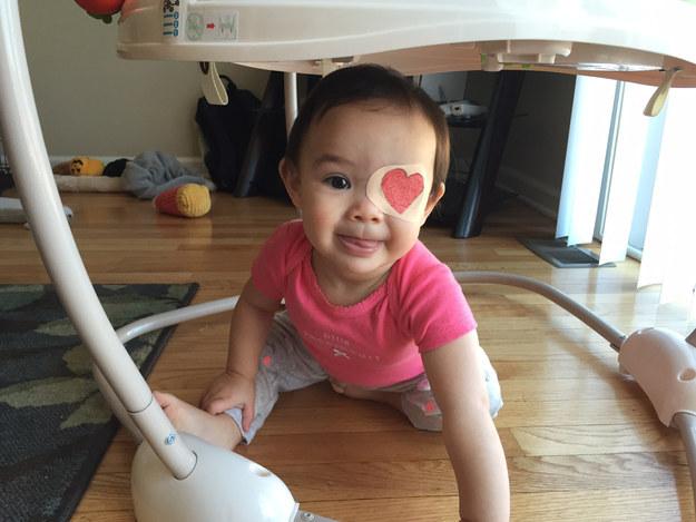 niña en el suelo usnado un parche en forma de corazón