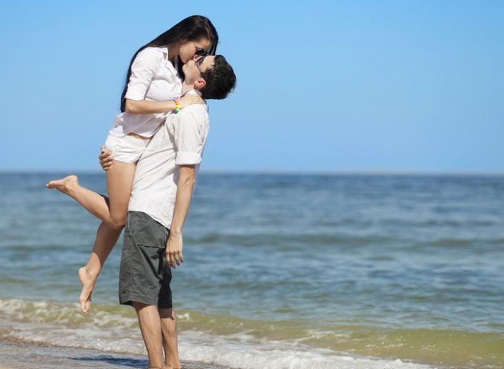 novio cargando a su novia y besándola en la playa